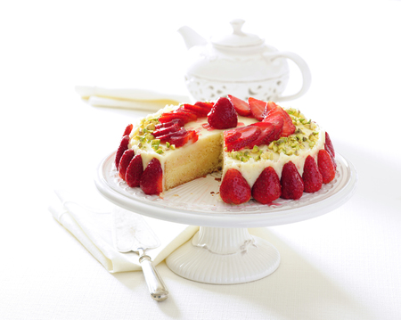 Cold cheesecake with fresh strawberries garnish with pistachio.