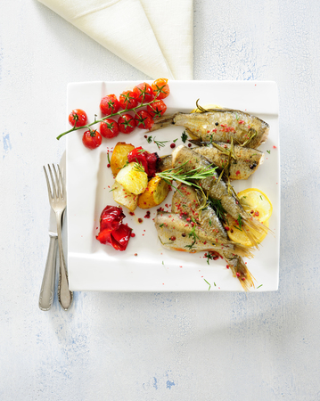 Baked whole fishe with lemon, herb and garlic butter served with baking potato.