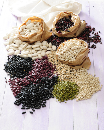 The different typs of common beans and legumes on white table.