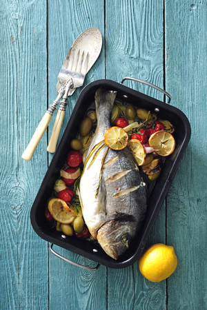 Oven baked whole sea fish with green olives, cherry tomatoes, lemon and herb butter.