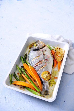 Oven baked whole sea fish with carrot, asparagus and herb butter. Stock Photo
