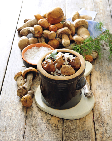 Polish or Russian salted pickled mushrooms in stoneware.