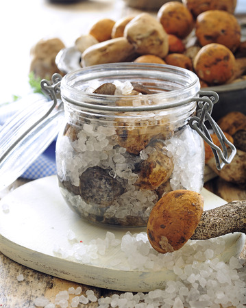 Polish or Russian salted pickled mushrooms in jars.