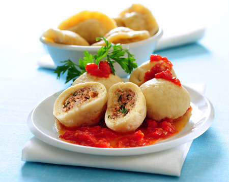 Ground meat filled dumplings with tomato sauce. 写真素材