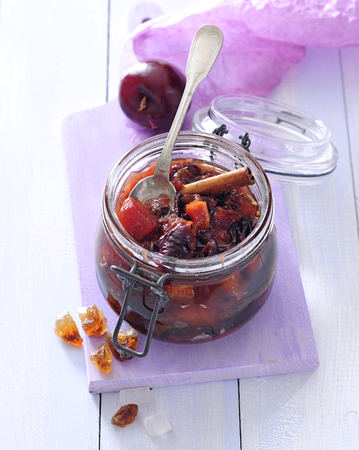 Sweet plums preserves with brown sugar and cinnamon stick.