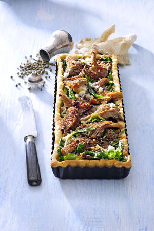Vegetarian tart with fried oyster mushroom and fresh spinach.