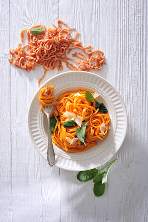 Orange linguine pasta with butter and sage sauce topped with parmesan cheese 스톡 콘텐츠