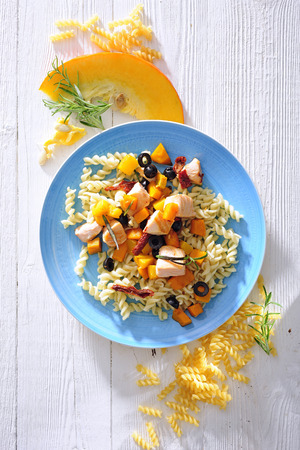 Fusilli pasta with fried salmon and pumpkin.