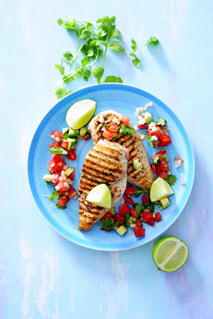 Mexican style grilled chicken breast fillet with tomato salsa. 스톡 콘텐츠
