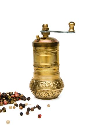 coffee grinder with scattered grains of spices around, isolated on white