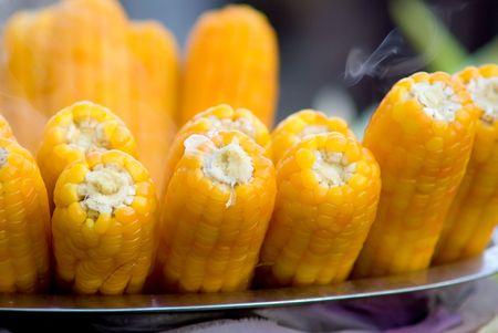 boiled yellow corn with smoke in pan