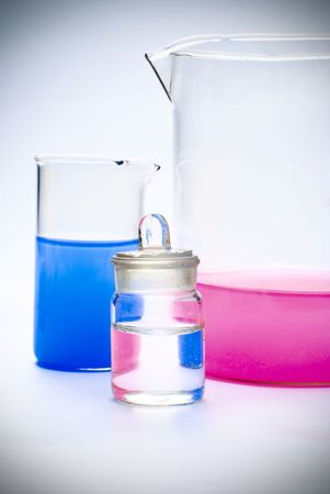 Transparent chemical glassware with red and blue solution Imagens