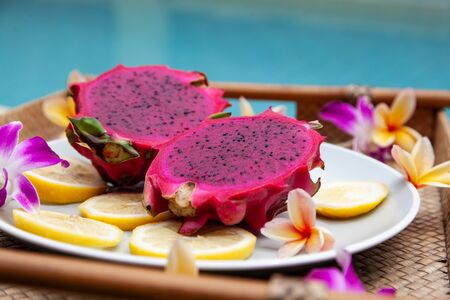 exotic dragonfruit red color on the background of turquoise water with flowers