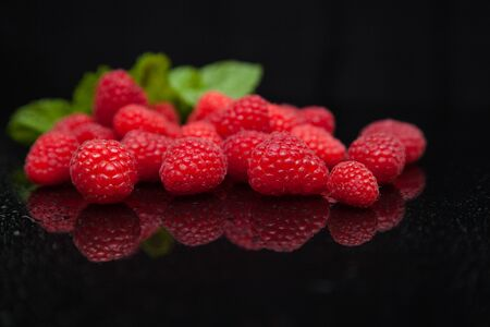 raspberries with mint leaves reflected on a black mirror table