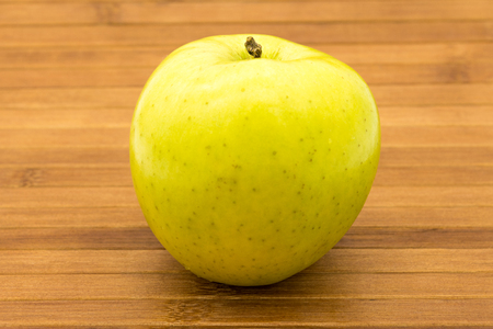 yellow apple: Yellow apple on wooden background