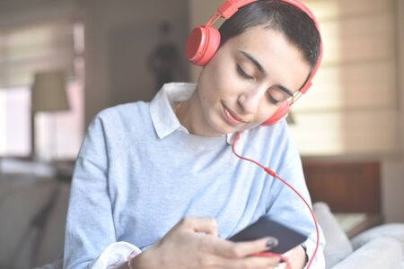 young girl with short hair listening to music 版權商用圖片