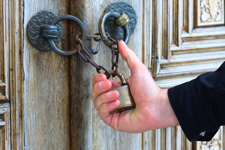 Hand holding old iron security lock of ornamental wooden door Stock Photo - 9459593