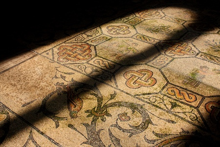 muster: Roman mosaic in old church illuminated by church window Stock Photo