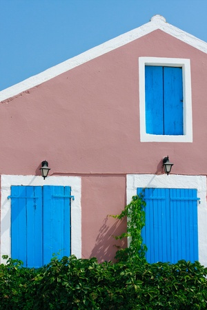 Traditional Greek village house with blue windows and doors photo