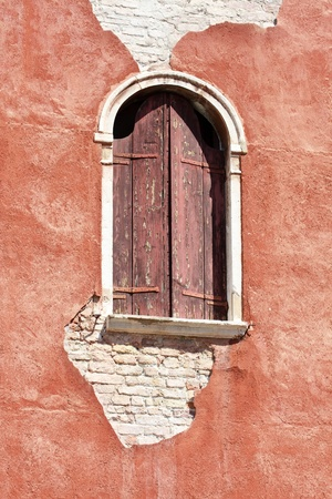 Venetian decayed facade with wooden window, Venice, Italy photo