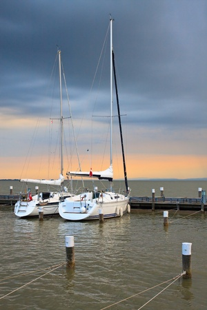 Stormy sunset with two yachts in marina photo
