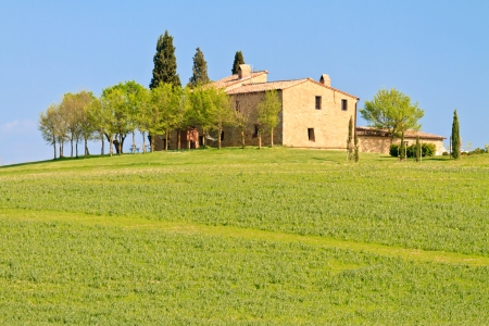 Picturesque tuscan farm house before blue sky, Italy