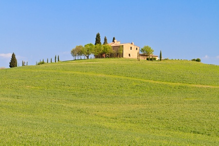 Picturesque tuscan farm house before blue sky, Italy photo