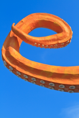 촉수: Tentacle of amusement park attraction against blue sky