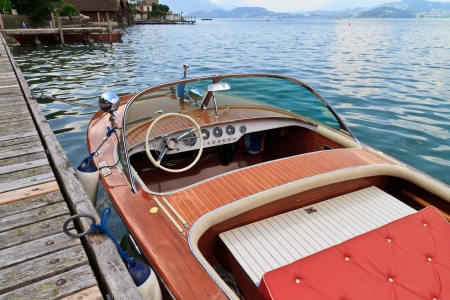 small boat: Classical wooden motor boat on alpine lake