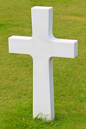 a memorial to fallen soldiers: Marble Cross of fallen Soldier, American War Cemetery near Omaha Beach, Normandy (Colleville-sur-Mer) Stock Photo