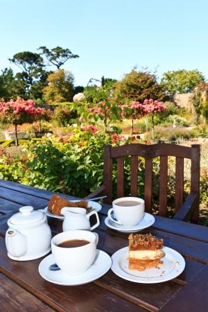 afternoon cafe: Ingl�s Cinco en punto de t� en el jard�n Foto de archivo