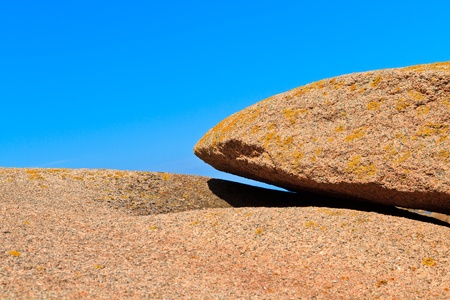 huge granite boulder on blue sky background photo