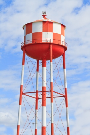 reservoir: Water tower with red and white stripes (blue sky background) Stock Photo