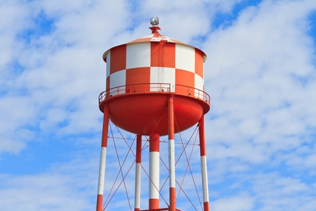 empty tank: Water tower with red and white stripes (blue sky background) Stock Photo