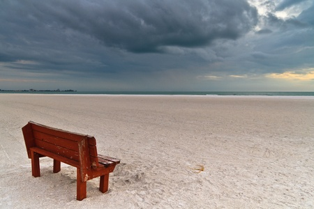 bad condition: Bench on white beach waiting for thunderstorm to come Stock Photo