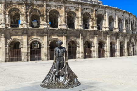 fight arena: Statue of matador Nime II in front of Roman Amphitheater in Nimes, France