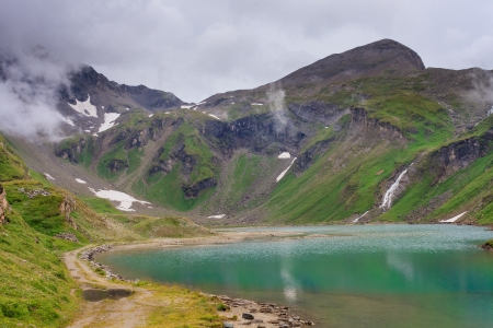 Alpine landscape with beautiful lake on a foggy day (near Grossglockner mountain, Austria) photo