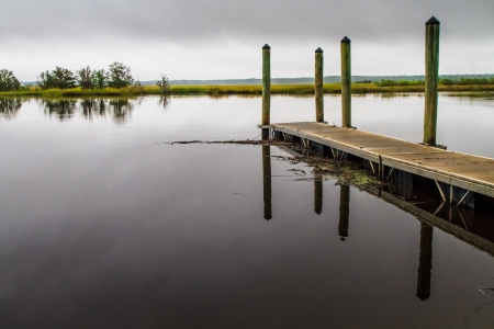 Wooden pier on a misty day reflecting in the water Stock Photo - 17501004
