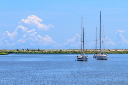anchoring: Three sailing boats anchoring near beach coastline