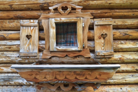 yukon: Window with heart shutters of a wooden log cabin in the European Alps Stock Photo