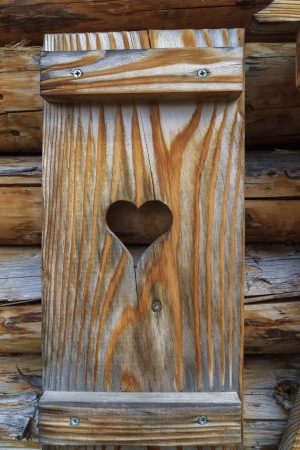 Window shutter with heart of a wooden log cabin in the European Alps photo