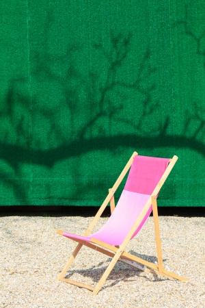 Folding Chair in front of green wall photo