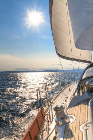 Yacht sailing towards sunset on blue sea photo