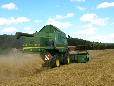 combines: Rear view of harvester on wheat field Stock Photo