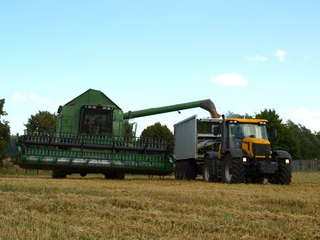 subsidy: A modern combine harvester emptying grain into a truck Stock Photo