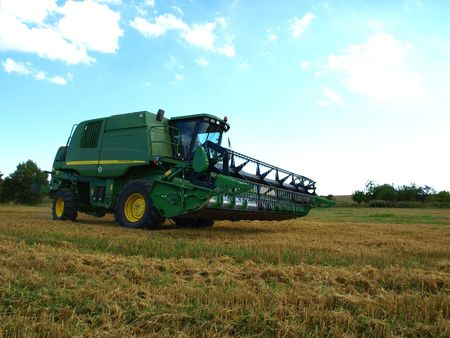 subsidy: Green Harvester on wheat field