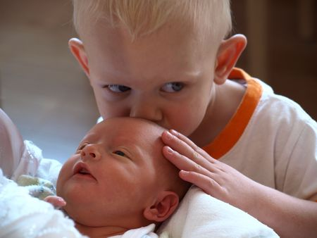 Young boy kissing his newborn sister Stock Photo - 5620919
