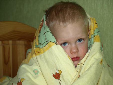 child stress: Sad looking boy under quilt