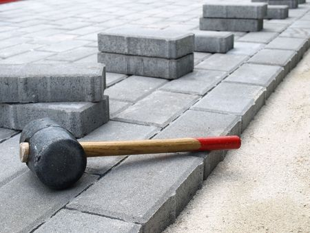 Bestrating in aanbouw. Rubber hamer op stenen blokken Stockfoto