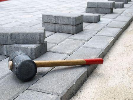 Pavimento en construcción. Martillo de goma en bloques de piedra  Foto de archivo